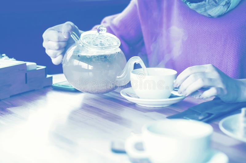 Hands of a girl in a cafe and drinking hot herbal tea. fragrant stock photography