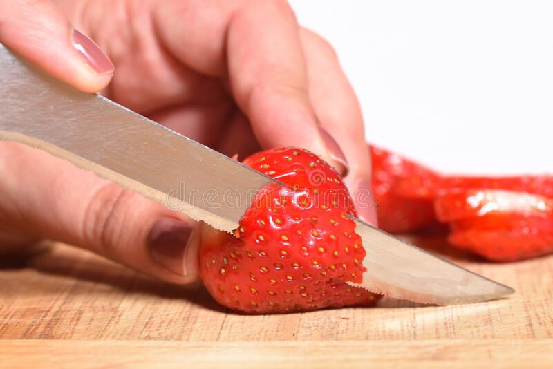 Hands of a girl is cutting fresh strawberries on kitchen counter preparing them to be blended with bananas for a smoothie or cake. Decoration stock photo