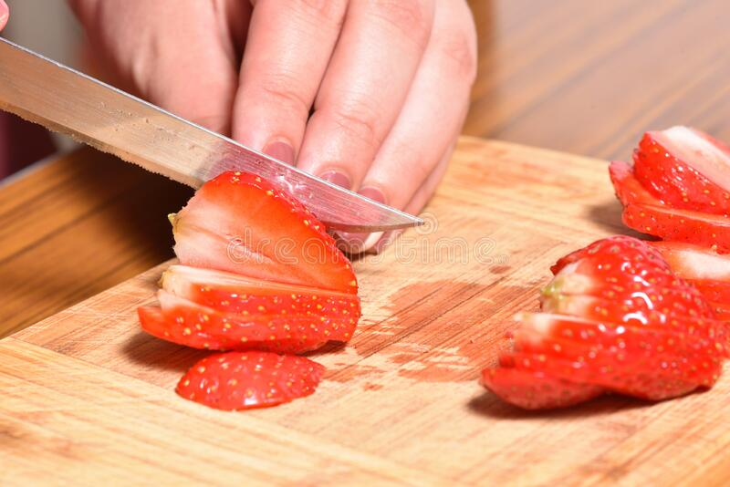 Hands of a girl is cutting fresh strawberries on kitchen counter preparing them to be blended with bananas for a smoothie or cake. Decoration royalty free stock photography