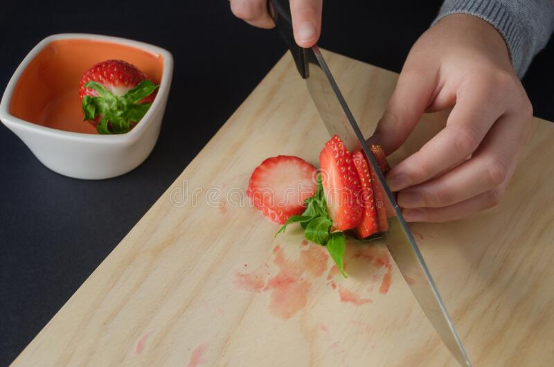Close-up of the hands of a girl cutting strawberries stock image