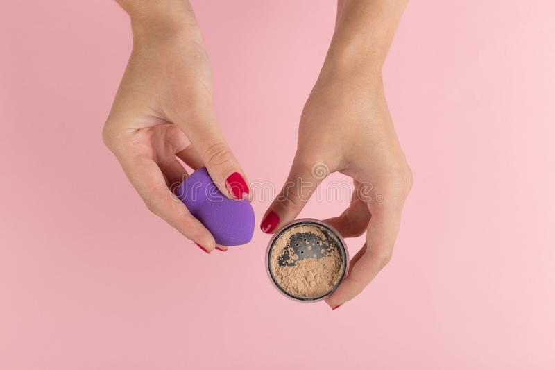 Hands of a girl holding a powder and a beauty blender for makeup on a pink background, copy space. Hands of a girl holding a powder and beauty blender for makeup royalty free stock image