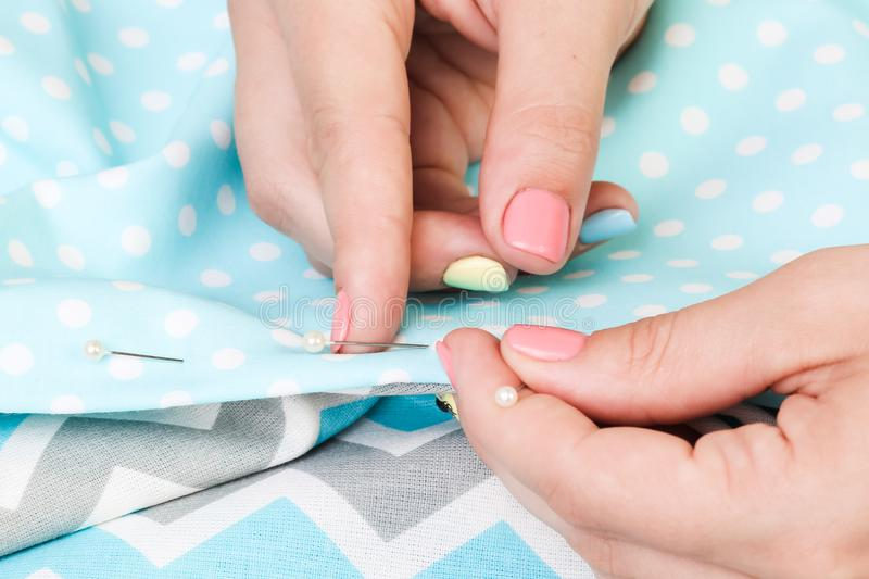 Hands of a girl with a needle and cloth. Handmade. Scrapbooking stock photo