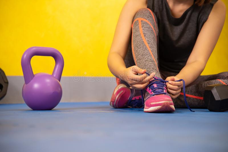 The hands of a girl`s shoelace and sneakers in the gym are ready stock photos