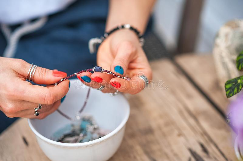 The hands of the girl touch the handmade jewelry. Girl and jewelry. Handmade woman decorating stones close up stock photo