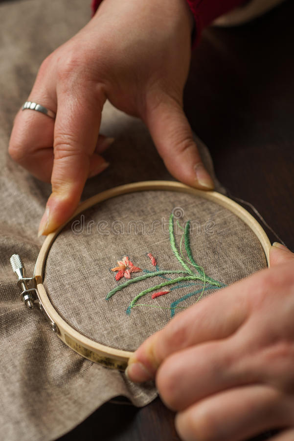 Embroidery. Hands of the girl working upon the embroidery stock image