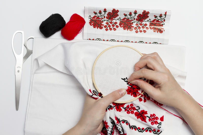 Hands girls embroider pattern using the frame. Hands girls embroider pattern red and black thread with the help of the frame royalty free stock images
