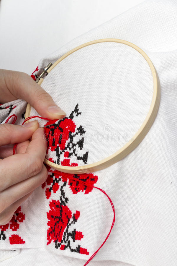Hands girls embroider pattern using the frame. Hands girls embroider pattern red and black thread with the help of the frame stock photography