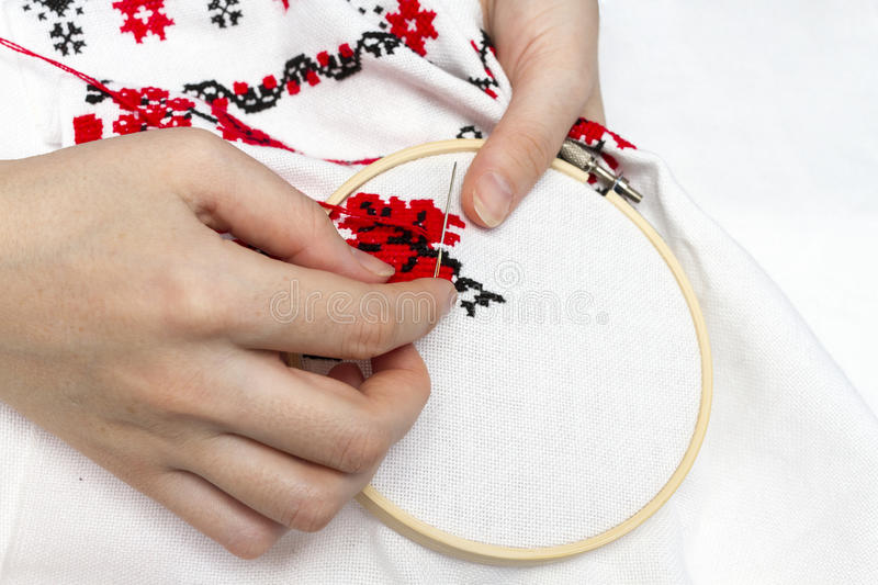 Hands girls embroider pattern using the frame. Hands girls embroider pattern red and black thread with the help of the frame stock photo