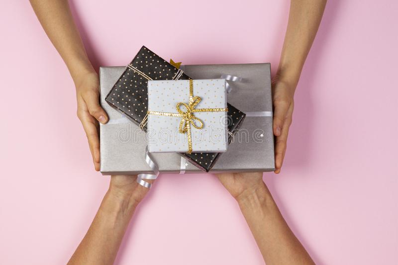 Hands give presents boxes over light pink background. Christmas, New Year, holidays concept stock image