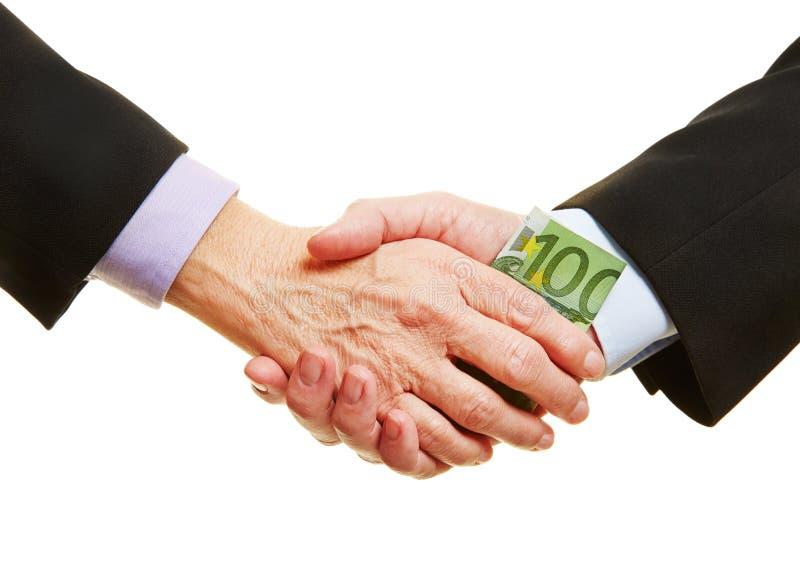 Hands giving Euro money bill for bribery. Hands giving Euro money bill for business bribery during handshake royalty free stock image