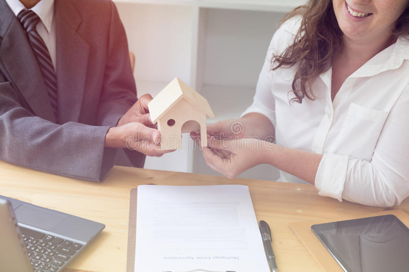 Hands giving house model to other hands with agreement on desk. House representing home ownership on a contract for mortgage loan - real estate business royalty free stock images