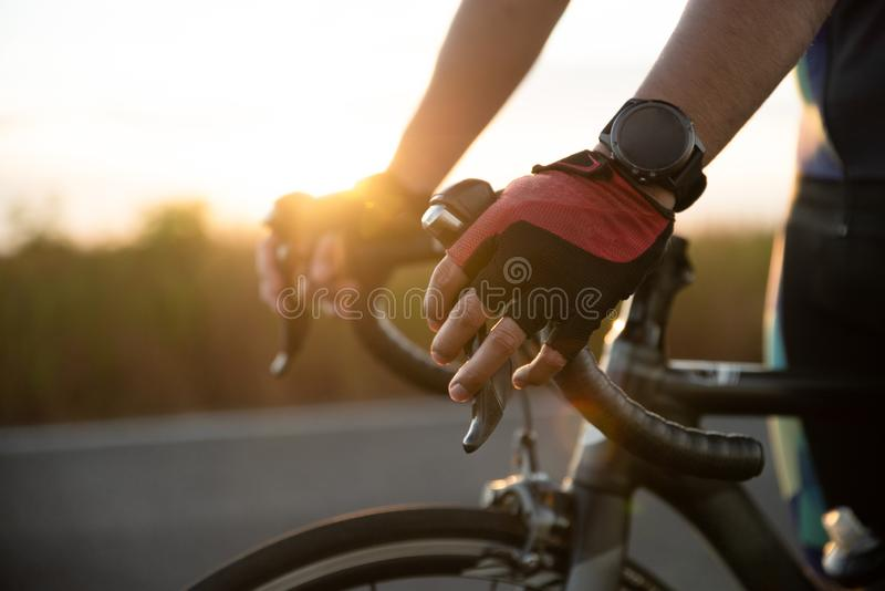 Hands in gloves holding road bicycle handlebar. Sports and outdoor activities concept.  royalty free stock image