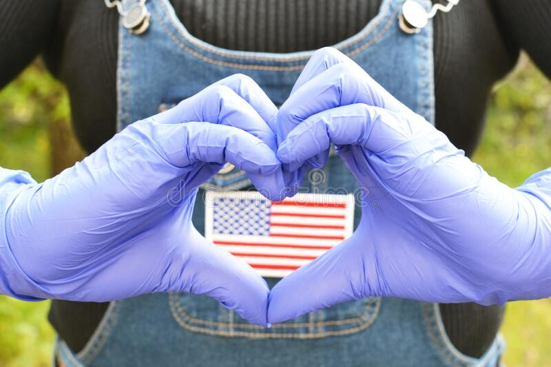 Hands in gloves with love gesture. On focus and the US flag on the clothes of a lady in the background royalty free stock photo