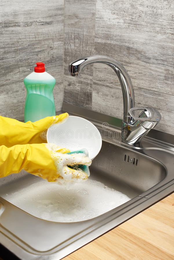 Hands in gloves washing tableware with sponge and detergent royalty free stock photography