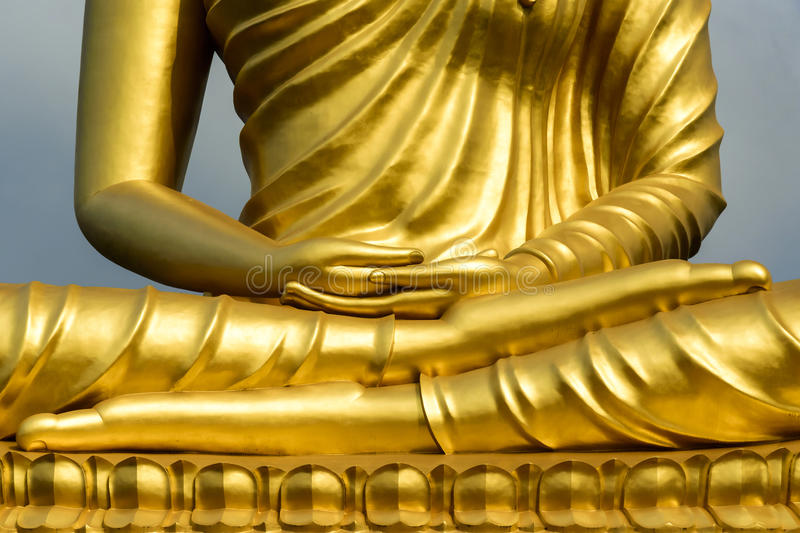 Hands of Golden Buddha statue royalty free stock photo