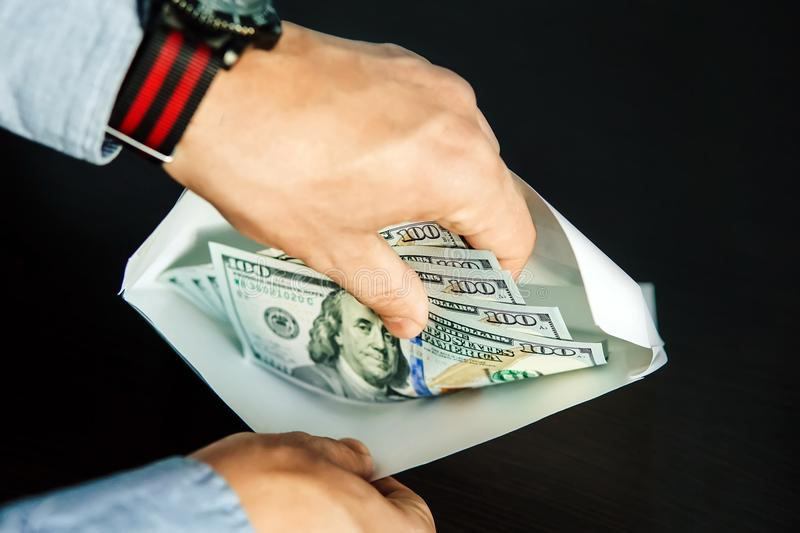Hands of grafter. He take US dollars from white envelope. Bribe-taker the brown wooden table. The employee believes illegal payment in a white envelope. Black stock image