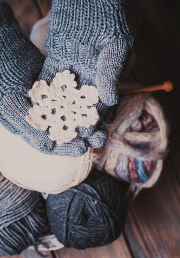 Hands in knitted gloves. Hands in a grey gloves holding white knitted snowflake as a winter symbol royalty free stock photos