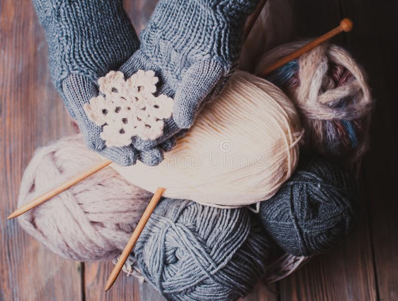 Hands in knitted gloves. Hands in a grey gloves holding white knitted snowflake as a winter symbol stock images