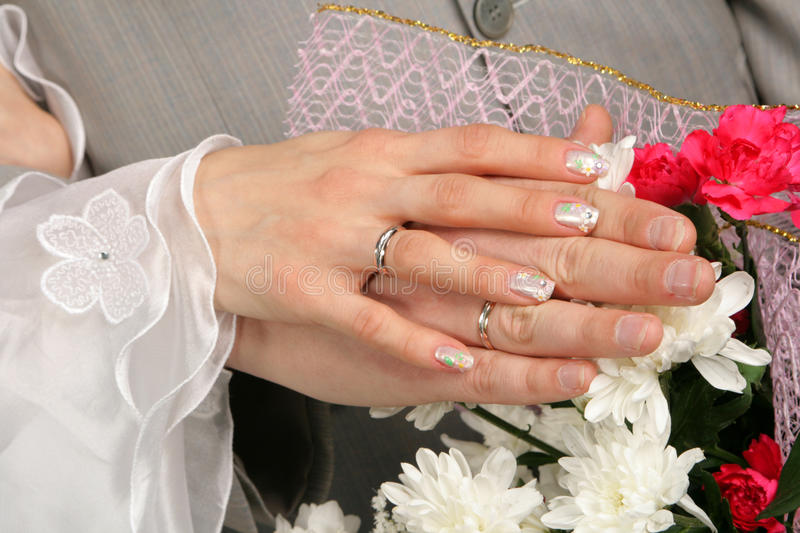 Hands of the groom and the bride. With wedding rings stock photos