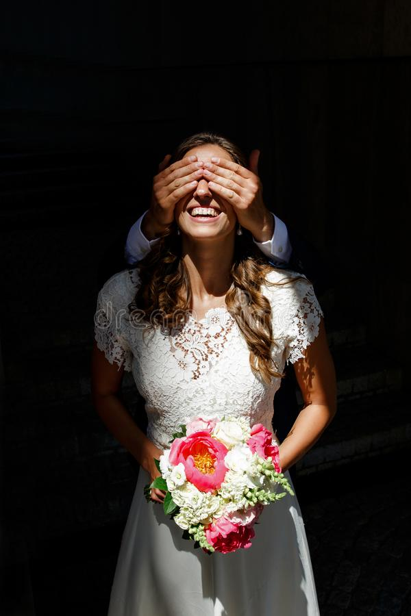 Hands of the groom close the eyes of the bride royalty free stock images
