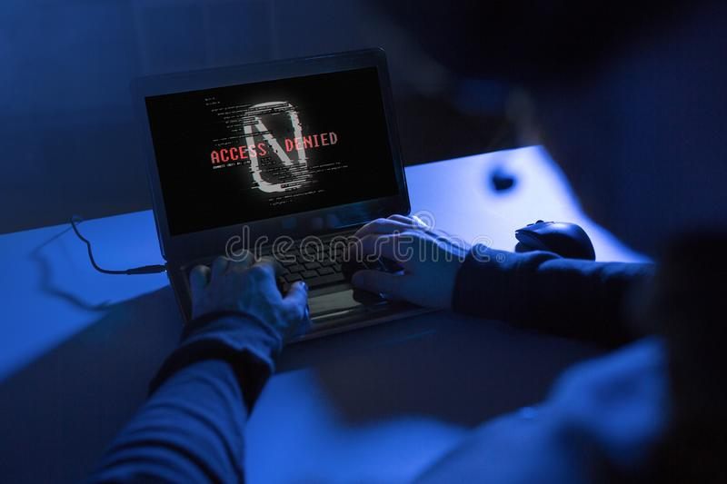 Hands of hacker with access denied message laptop. Cybercrime, hacking and technology concept - hands of hacker with access denied message on laptop computer stock photography