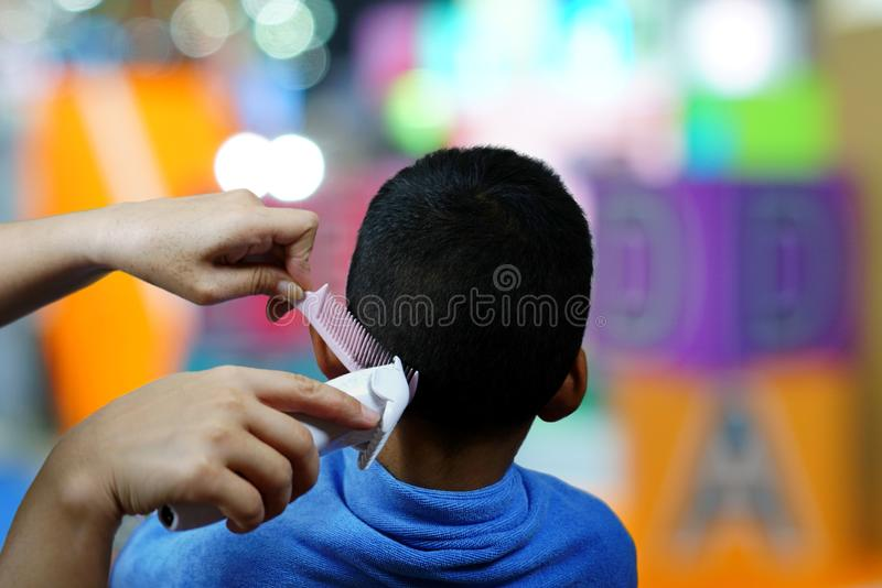 Hands of hairstylist cutting hair little boy using comb and clipper in barbershop royalty free stock photos