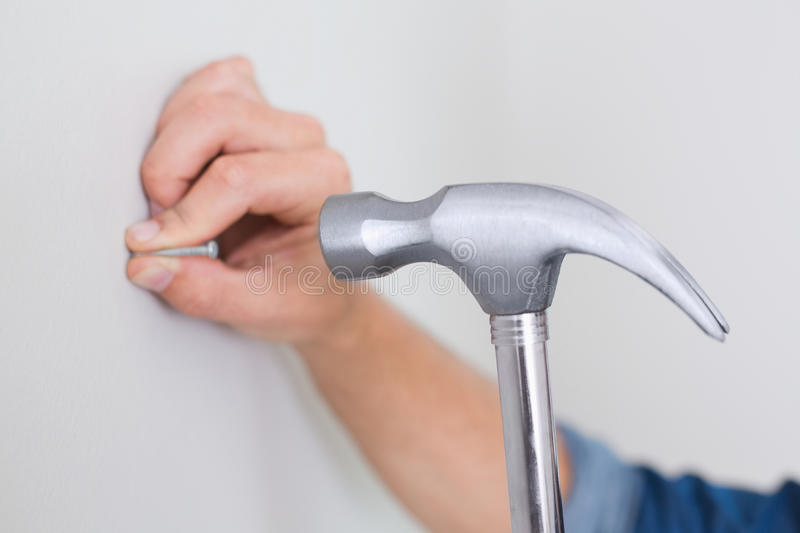Hands hammering nail in wall royalty free stock image