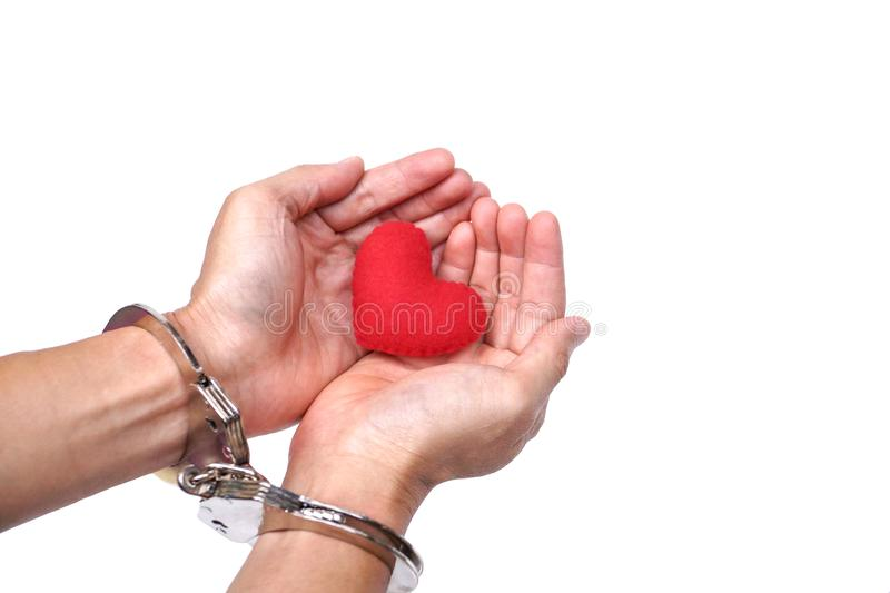 Hands with handcuffs holding a red heart stock photography