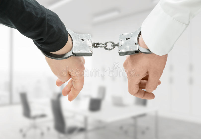 Hands in handcuffs. Hands of two men fixed in handcuffs. Close up. Blurred office background. Concept of accessory of crime royalty free stock image