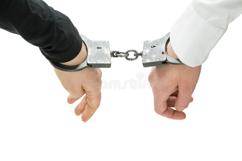 Hands in handcuffs. Hands of two men fixed in handcuffs. Close up. Isolated. Concept of accessory of crime stock photo