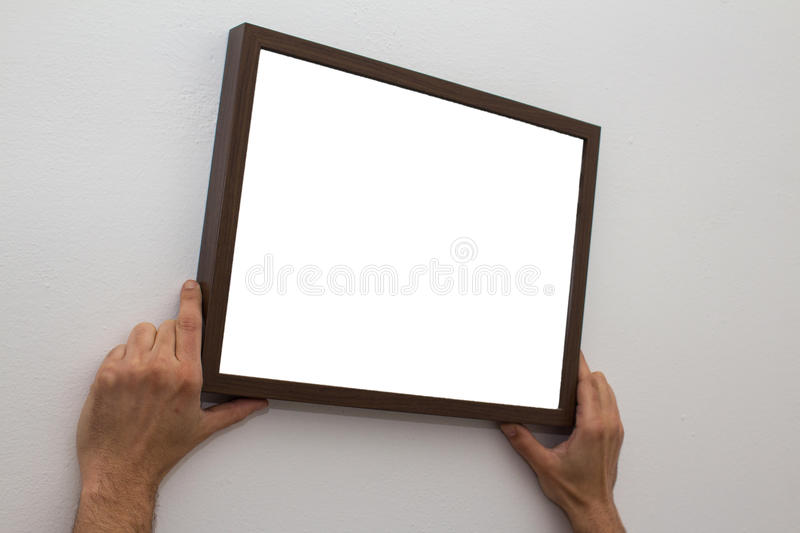 Hands hanging blank picture frame on wall stock image
