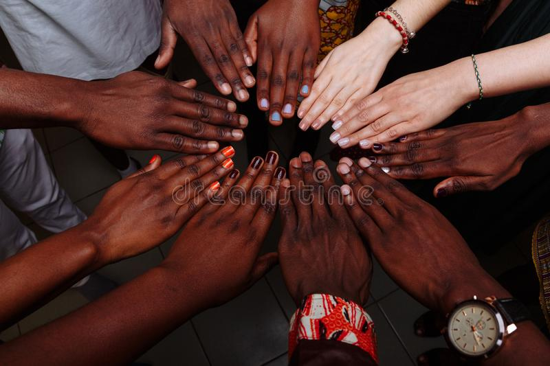 Hands of happy group of multinational African, latin american and european people which stay together in circle.  royalty free stock images