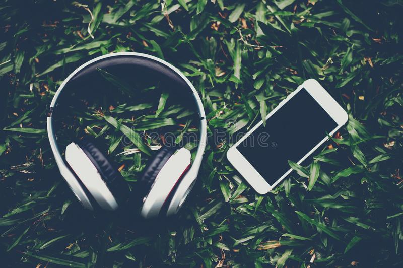Hands and headphones are placed next to each other in green grass and moody music. Concepts of communication and listening. stock image