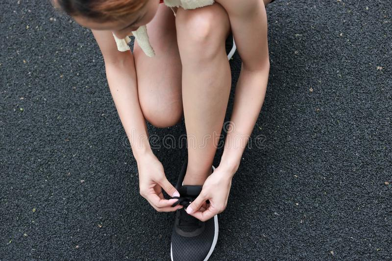 Hands of healthy Asian woman tying shoelaces on running shoes on the street. Fitness and workout wellness concept. stock photography