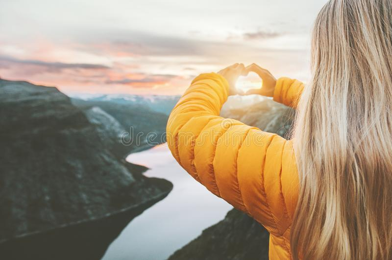 Hands heart love symbol shaped woman traveling. Lifestyle charity help concept vacations in Norway sunset mountains and lake landscape stock images