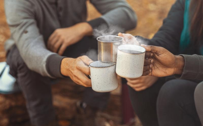 Hands of hikers cheering up with camping cups royalty free stock photos