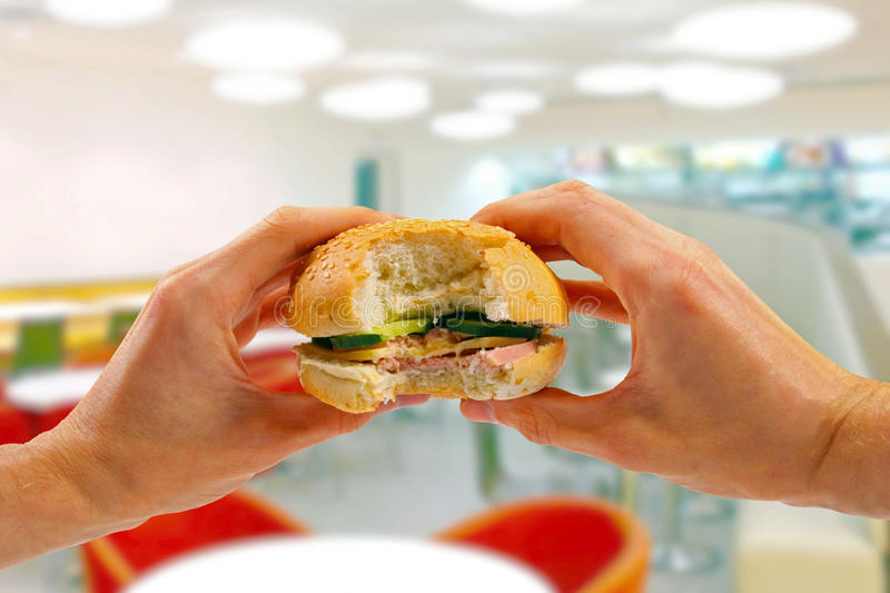 Hands hold a burger in fast food restaurant. Blurred background stock photography