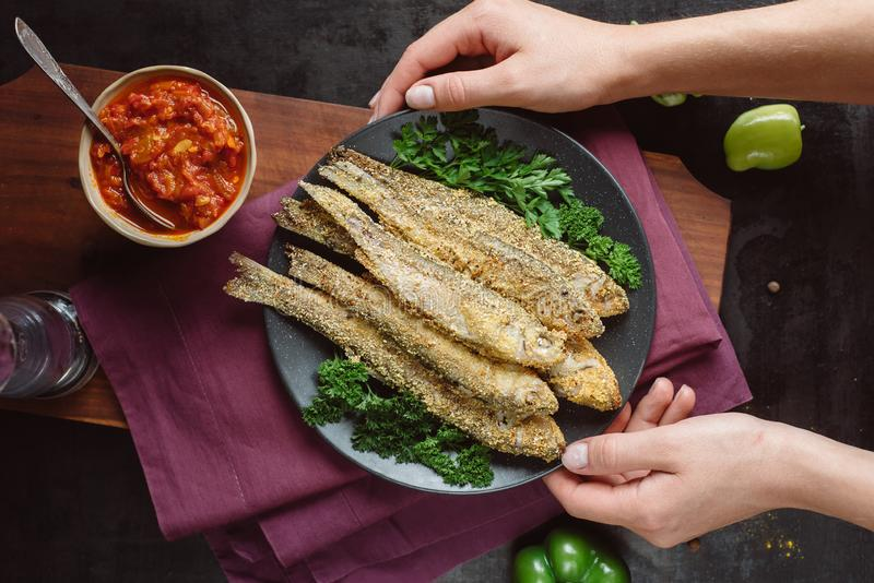 Hands hold Fried fish in a plate with tomato sauce, greens and peppers on wooden board and a dark background royalty free stock photos