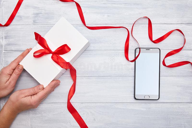 Hands hold Gift Box with red ribbon and smartphone on a woodem background royalty free stock photography