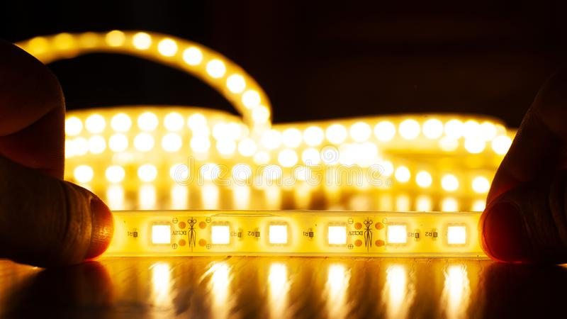 Hands hold a LED strip of a warm spectrum, installation of diode light. Close-up royalty free stock image