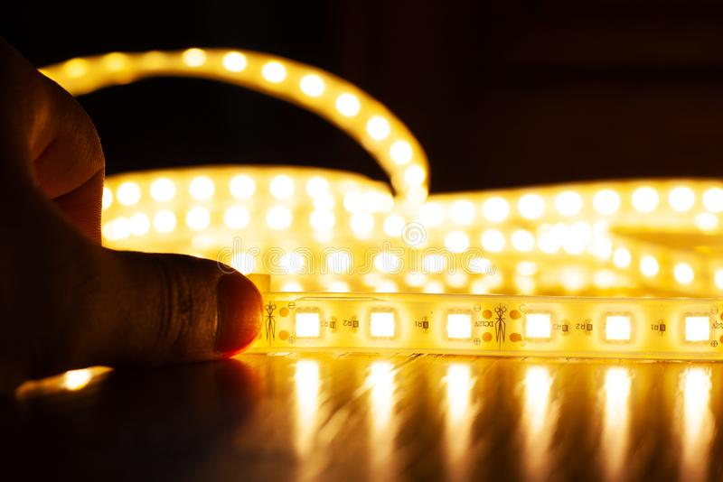 Hands hold a LED strip of a warm spectrum, installation of diode light. Close-up stock photo