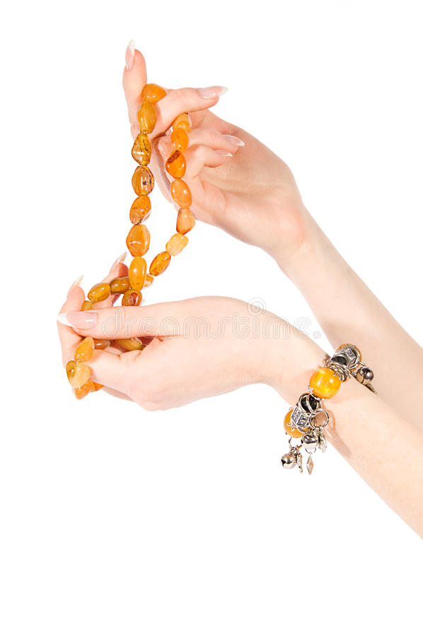 Hands holding amber necklace and bracelet. Woman hands holding amber necklace and bracelet on white stock photos