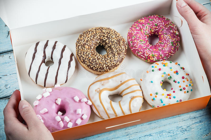 Hands holding assorted donuts stuffed. In a box stock photo