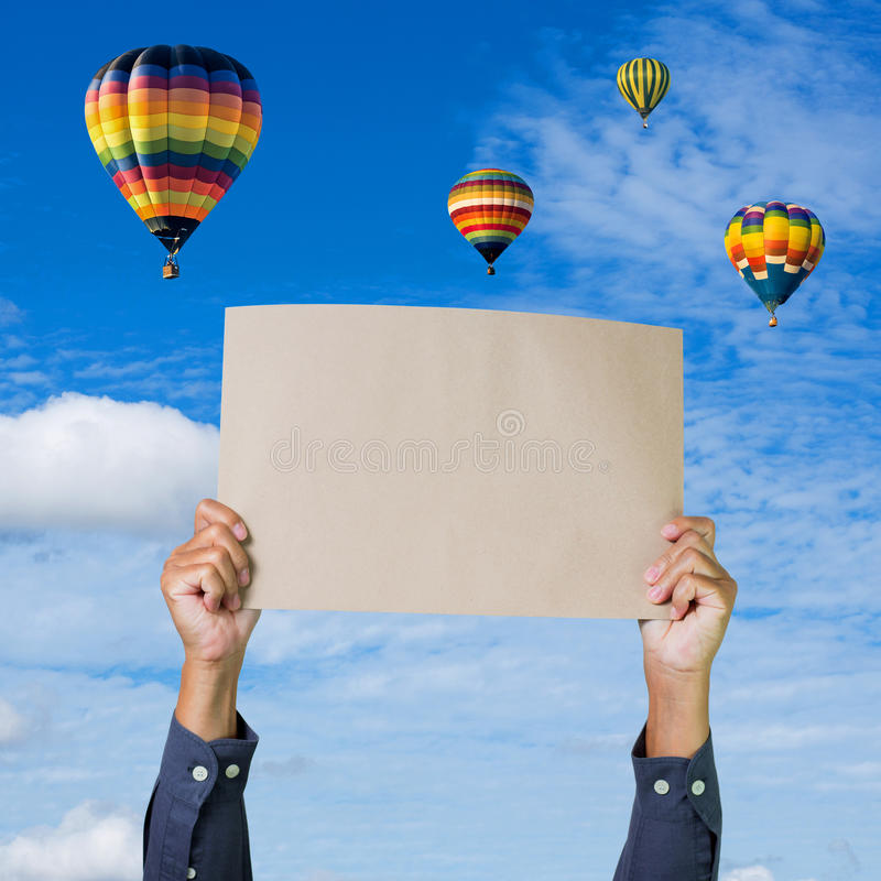 Hands holding banner with hot air balloon and blue sky background stock photo