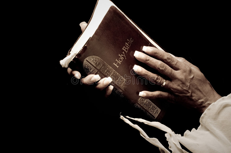 Hands holding bible. African american woman's hands holding bible