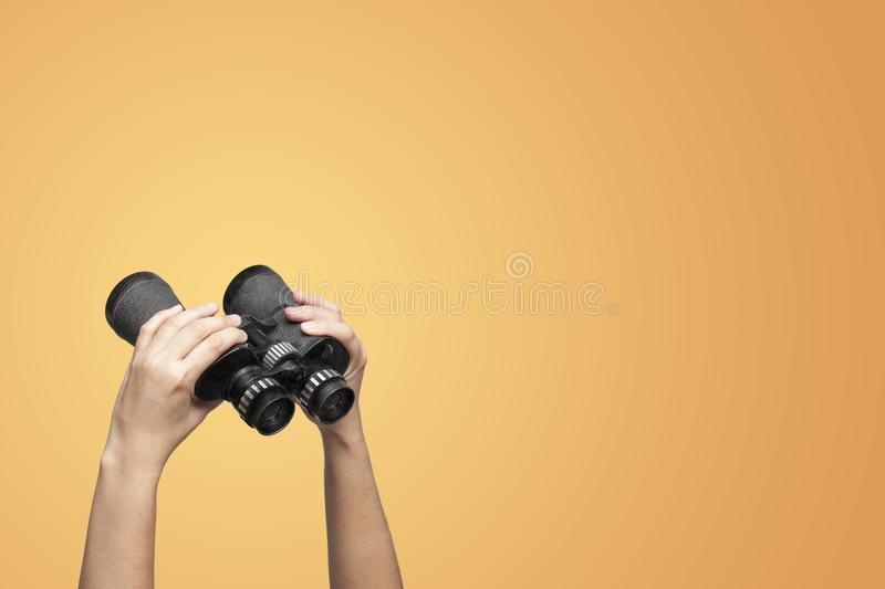 Hands holding binoculars on yellow background stock photography