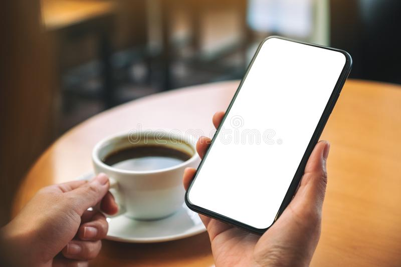 Hands holding black mobile phone with blank desktop screen while drinking coffee. Mockup image of hands holding black mobile phone with blank desktop screen stock photo