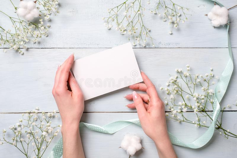 Hands holding blank paper card on light blue wooden desk with flowers. Tender greeting card for womens or mothers day, easter, spr royalty free stock photo