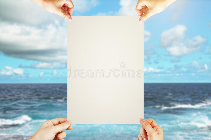 Hands holding blank poster. Four hands holding blank poster on sea and sky background. Mock up stock images