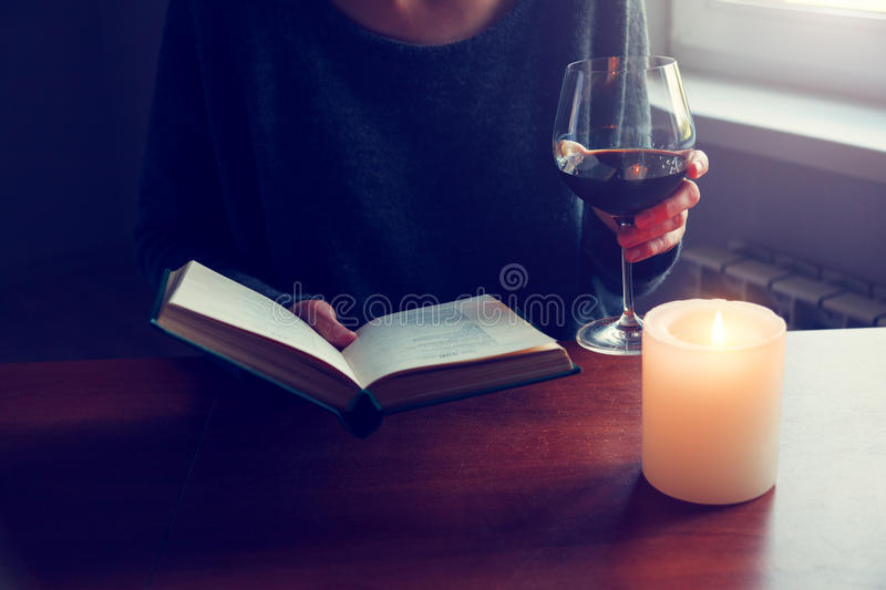 Hands holding book and reading with wine royalty free stock images